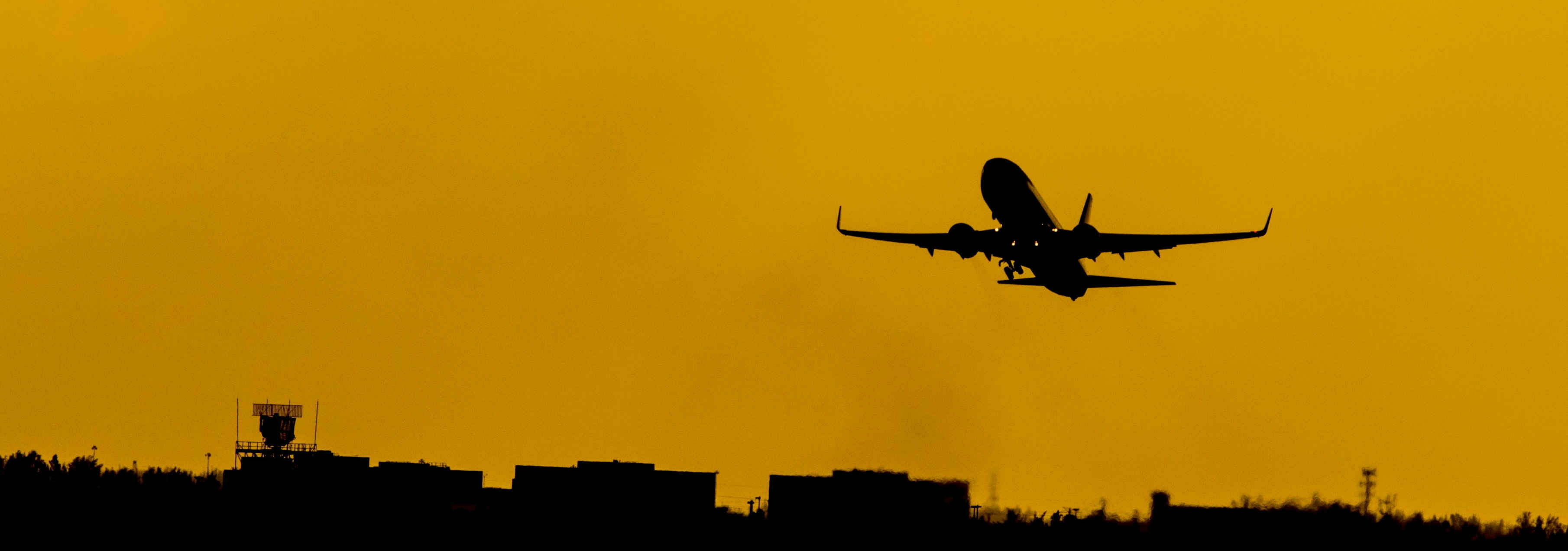 The departure of a plane, representing the link between foreign experiences and unethical behavior.